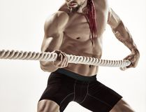 Attractive muscular man working out with heavy ropes. Stock Photos