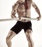 Attractive muscular man working out with heavy ropes. Royalty Free Stock Images
