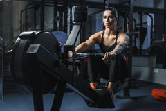 Attractive muscular woman CrossFit trainer do workout on indoor rower