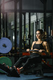 Attractive muscular woman CrossFit trainer do workout on indoor rower Stock Image