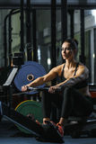 Attractive muscular woman CrossFit trainer do workout on indoor rower royalty free stock image