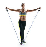 Attractive muscular woman performs exercises for deltoid muscles using an resistance bands Stock Photo