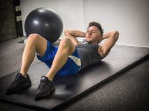 Handsome young man doing abs exercises on mat. Attractive muscular young man in gym working out, doing exercises for abs on the ground stock photos