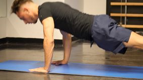 Handsome young man doing push-ups exercise on mat