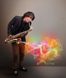 Attractive musician playing on saxophone with colorful abstract Royalty Free Stock Photography