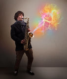 Attractive musician playing on saxophone with colorful abstract Royalty Free Stock Photo