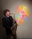 Attractive musician playing on saxophone with colorful abstract Royalty Free Stock Photos