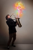 Attractive musician playing on saxophone with colorful abstract Stock Image