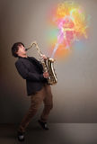 Attractive musician playing on saxophone with colorful abstract Stock Photo