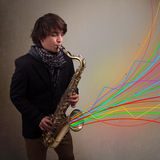 Attractive musician playing on saxophone while colorful abstract Stock Photo