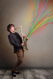 Attractive musician playing on saxophone while colorful abstract Royalty Free Stock Image