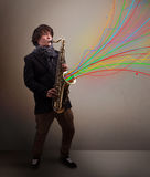 Attractive musician playing on saxophone while colorful abstract Stock Image