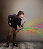 Attractive musician playing on saxophone while colorful abstract Royalty Free Stock Photo