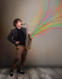 Attractive musician playing on saxophone while colorful abstract Stock Images