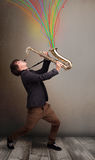 Attractive musician playing on saxophone while colorful abstract Stock Photos