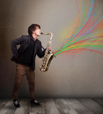 Attractive musician playing on saxophone while colorful abstract Royalty Free Stock Photos