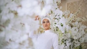 Attractive muslim bride with tiara in weddind dress in white flowers. Horizontal Stock Images