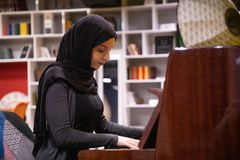 Attractive Muslim female in a hijab playing piano royalty free stock images