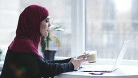 Attractive muslim girl with hijab on her head is drinking cappuccino while searching for something on her smartphone. Indoors footage stock video