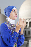 Attractive muslim girl praying at mosque. Beautiful muslim girl in blue praying at mosque Stock Photography
