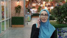 Attractive muslim girl talking on the phone and smiling. Arabic stock footage