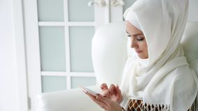 Attractive muslim woman in hijab is browsing internet pages in smartphone sitting on the sofa. stock video footage