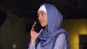 Attractive Muslim woman in hijab talking at mobile phone stock video footage