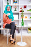 Attractive muslim woman sitting and drining a cup of tea Royalty Free Stock Photo