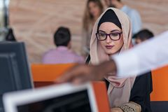 Attractive Muslim young woman working in office on computer.  Stock Images