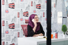 Attractive Muslim young woman working in office on computer Stock Photos