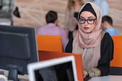 Attractive Muslim young woman working in office on computer.  Royalty Free Stock Image
