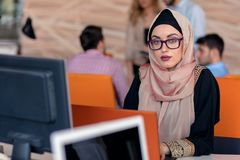 Attractive Muslim young woman working in office on computer. Attractive Muslim young women working in office on computer Stock Photos