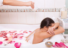 Attractive naked girl enjoys a bath with milk and rose petals Royalty Free Stock Photography