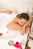 Attractive naked girl enjoys a bath with milk and rose petals Stock Photography