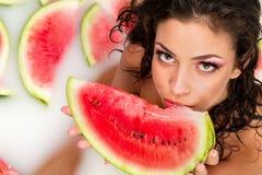 Girl enjoys a bath with milk and watermelon. royalty free stock photos