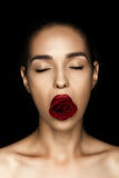 Attractive naked woman with closed eyes holding red rose in lips. Isolated on black Stock Image