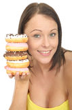 Attractive Natural Happy Young Woman Holding a Pile of Iced Donuts Stock Photos
