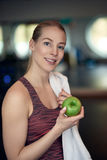 Attractive natural young woman athlete holding a fresh crisp green apple royalty free stock image