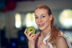 Attractive natural young woman athlete holding a fresh crisp green apple royalty free stock photos