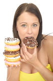Attractive Natural Young Woman Eating a Pile of Iced Donuts Stock Photos
