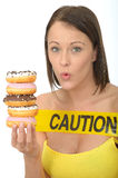 Attractive Natural Young Woman Holding a Pile of Iced Donuts with Caution Sign Stock Photos