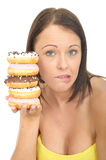 Attractive Natural Young Woman Holding a Pile of Iced Donuts with Guilty Facial Expression Stock Photo