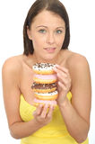 Attractive Natural Young Woman Holding a Pile of Iced Donuts Royalty Free Stock Photos