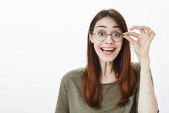 Attractive nerdy girl fascinated to see new book in store. Good-looking overwhelmed woman in casual t-shirt, smiling. Broadly, seeing something surprising and Royalty Free Stock Photos