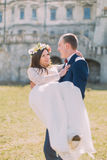 Attractive newlywed couple at green lawn near beautiful ruined baroque palace. Loving groom holding charming bride on Stock Photos