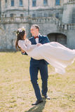 Attractive newlywed couple at green sunny lawn near beautiful ruined baroque palace. Loving groom holding charming bride Stock Photo