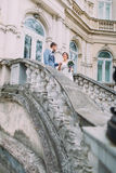 Attractive newlywed couple in love going down by ancient stairs near the old austrian palace Stock Photography