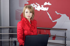 Attractive news television presenter. Beautiful news Television Presenter in front of the laptop looking at the camera Stock Images