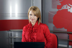 Attractive news television presenter. Beautiful news Television Presenter in front of the laptop looking at the camera Stock Image