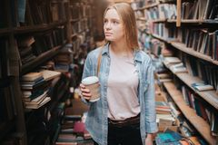 Attractive and nice girl is standing among big and long bookshelfs with old books. She is holding a cup of coffe in her. Hand and looking to the shelf. The royalty free stock photography